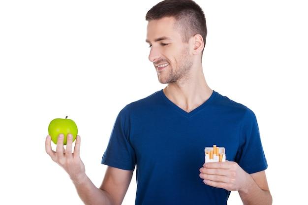 Eu fiz minha escolha. jovem confiante olhando para a maçã na mão, enquanto segura o maço de cigarros na outra mão e isolado no branco