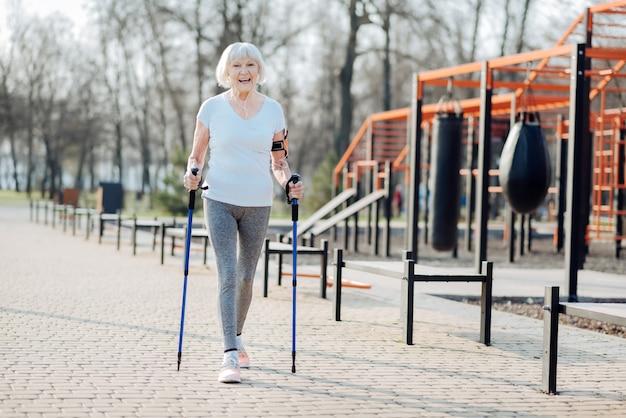 Eu gosto de esporte. mulher loira inspirada sorrindo e caminhando com a ajuda de muletas