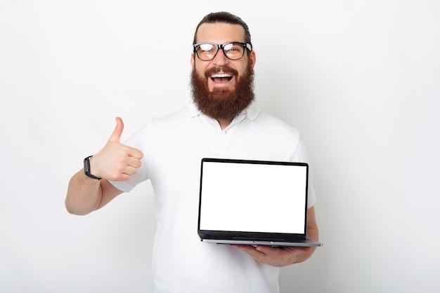 Eu gosto dessa oferta. homem barbudo está segurando o polegar e um laptop aberto.