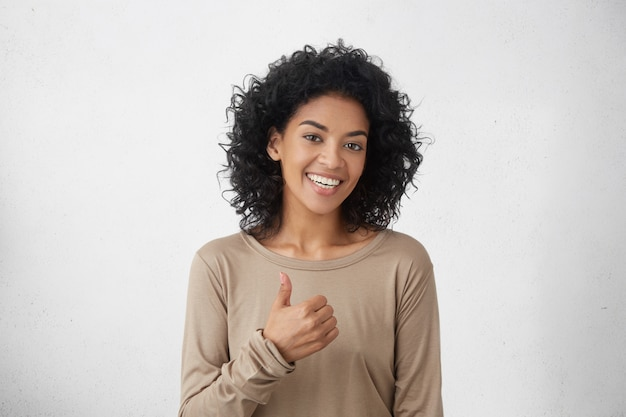 Eu gosto disso. bom trabalho. feliz fêmea jovem de pele escura, vestindo camiseta de mangas compridas casual, fazendo os polegares para cima o sinal e sorrindo alegremente, mostrando seu apoio e respeito a alguém. linguagem corporal