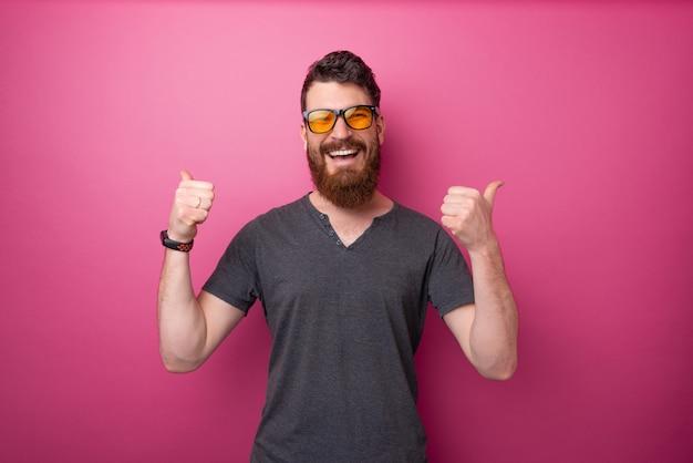 Eu gosto disso!! homem barbudo fazendo uma festa com o polegar para cima, fundo rosa isolado