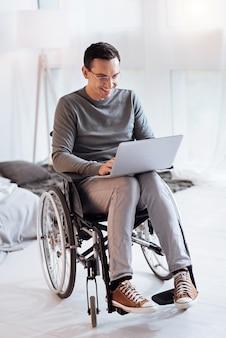 Eu gosto disso. homem bonito com um sorriso no rosto e abaixando a cabeça enquanto olha para a tela do computador