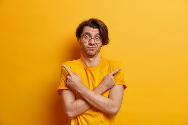 Eu me pergunto o que escolher. hesitante cara hipster cruza as mãos sobre pontos no peito em diferentes direções, vestido com uma camiseta casual isolada sobre a parede amarela, sem saber qual é a melhor decisão