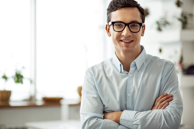 Eu me sinto feliz. atraente alegre homem de cabelos escuros sorrindo, usando óculos e com os braços cruzados