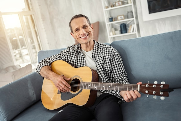 Eu me sinto feliz. homem bonito, alegre e bem construído sorrindo e tocando violão enquanto está sentado no sofá