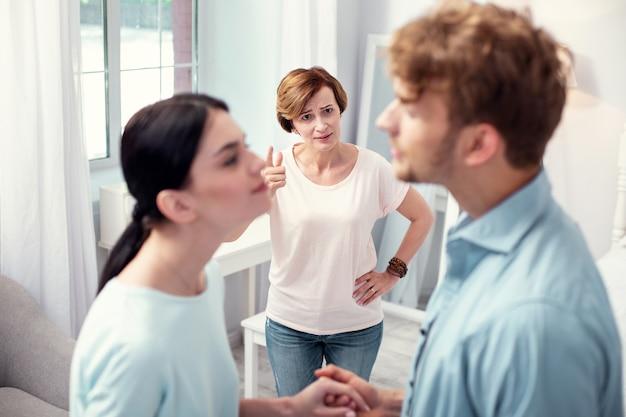 Eu não aprovo. mulher idosa infeliz olhando para o casal sem aprovar seus relacionamentos