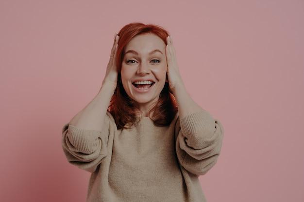 Eu não consigo acreditar nos meus olhos! mulher jovem emocional surpreendida com o cabelo ruivo tocando a cabeça com as duas mãos e mantendo a boca aberta de empolgação, vestida com um macacão bege, isolada sobre um fundo rosa