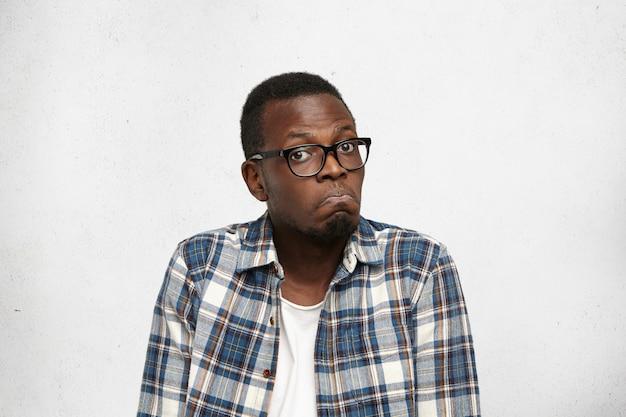 Eu não faço ideia. retrato de homem afro-americano jovem confuso em copos, encolher os ombros os ombros, com olhar hesitante e duvidoso, estragar os lábios. expressões faciais humanas e emoções