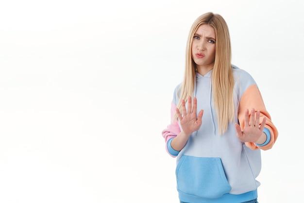 Eu não gosto disso retrato de menina loira decepcionada e insatisfeita afastada, levantando as mãos para parar, rejeição