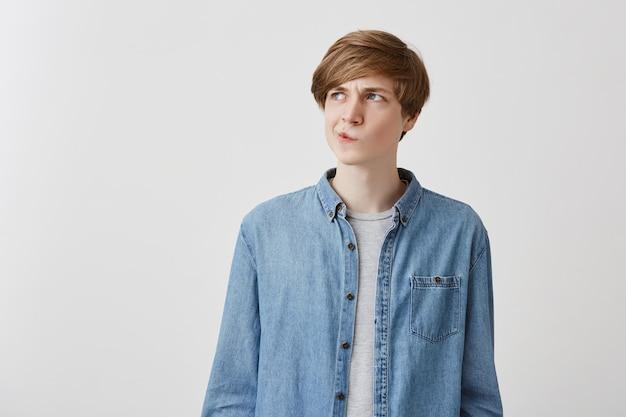 Eu não sei. homem caucasiano jovem duvidoso, vestindo camisa jeans, fazendo beicinho e olhando com expressão indecisa no rosto, mostrando dúvida e hesitação. linguagem corporal e expressão facial