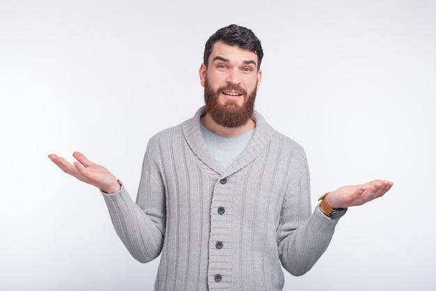 Eu não sei! jovem homem barbudo está gesticulando em branco.