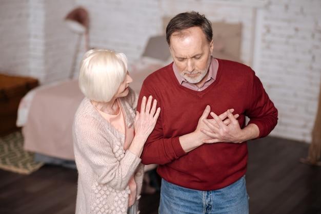 Eu não sou bom. retrato de um homem idoso em pé e tocando a área do coração, enquanto sua amorosa esposa o apoiava durante este tempo.