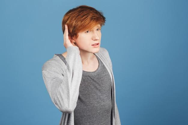 Eu não te ouço. copie o espaço. close-up de cara bonito sério com cabelo vermelho em roupas casuais, segurando a mão perto da orelha, tentando ouvir o que seu amigo está dizendo no café barulhento