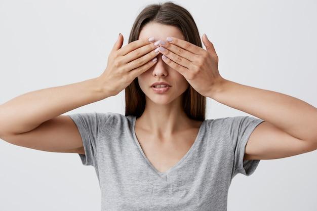 Eu não vejo nada. retrato de mulher jovem bonita caucasiana sexy estudante com cabelo comprido escuro em roupas de camiseta cinza olhos com as mãos com expressão séria e calma do rosto. linguagem corporal.