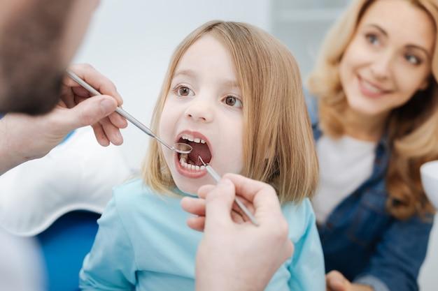 Eu os escovo regularmente. criança adorável e corajosa visitando um dentista e se comportando como uma boa menina, enquanto a mãe está sentada ao lado dela