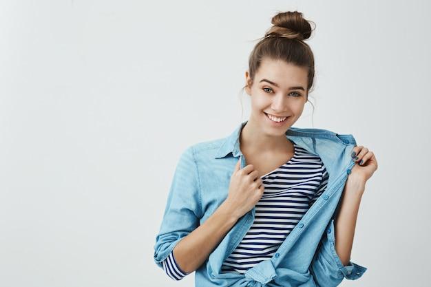 Eu posso te emprestar minha camisa. retrato interior de legal atraente mulher europeia com penteado de coque, tirando a roupa jeans enquanto sorrindo com sorriso intrigado e flertar.