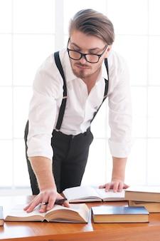 Eu preciso de mais informações. jovem pensativo de camisa e suspensórios, inclinado à mesa e lendo um livro sobre ela
