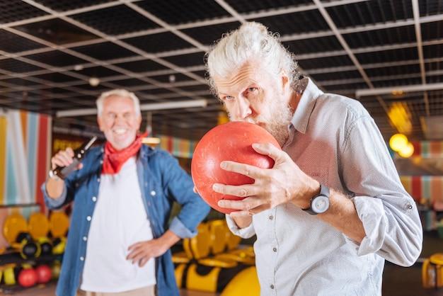 Eu preciso de sorte. homem idoso sério beijando a bola enquanto se prepara para jogá-la