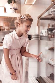 Eu quero isso. linda garota feliz apontando com o dedo enquanto escolhe um bolo para comer