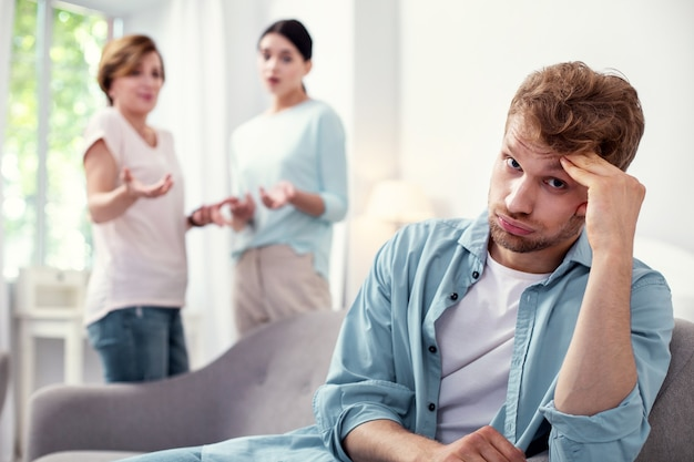 Eu quero paz. homem triste e triste ouvindo sua esposa e sua mãe enquanto está cansado de brigas