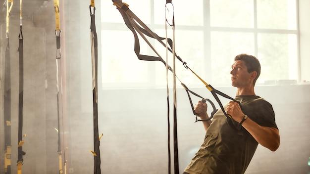 Eu quero ter um corpo perfeito. homem forte e atlético treinando seus braços com alças trx fitness no ginásio.