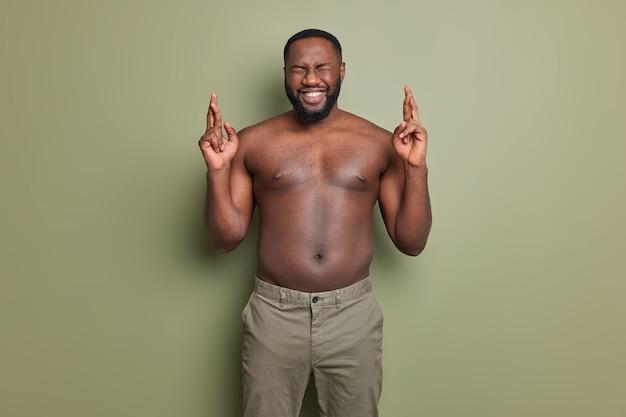 Eu quero vencer. homem afro-americano de pele escura positiva cruza os dedos, faz desejo e tem esperança em poses melhores com o torso nu