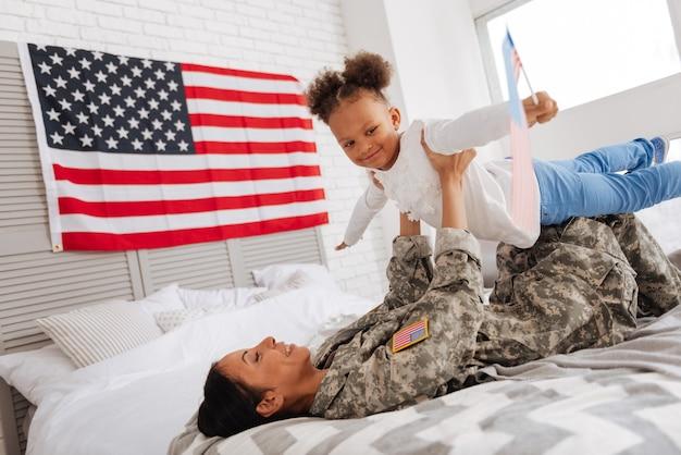 Eu seguro você. mulher bonita divertida e enérgica fazendo sua filha se sentir como um pássaro enquanto se diverte na cama e passa a manhã juntos