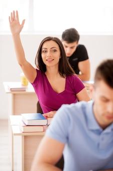 Eu sei a resposta! linda aluna sentada à mesa levantando a mão