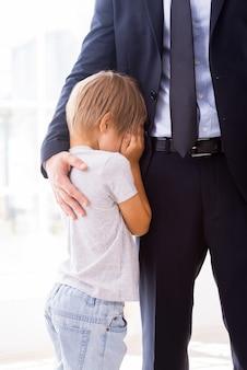 Eu sentirei saudades de você! menino chorando e cobrindo o rosto com as mãos enquanto o pai em traje formal o consola