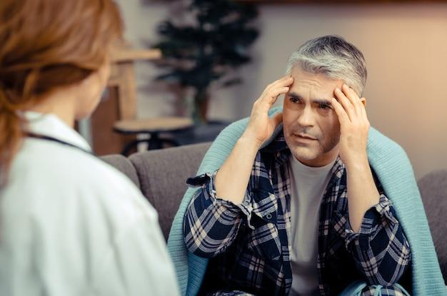 Eu sinto dor. homem maduro e triste segurando as têmporas enquanto fala com o médico