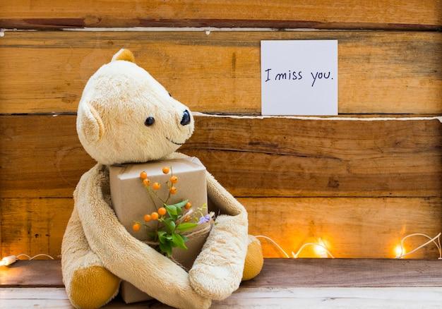 Eu sinto sua falta caligrafia de cartão de mensagem com ursinho segurando a caixa de presente
