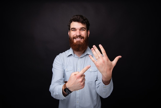 Eu sou casado! jovem barbudo apontando para seu anel de casamento na mão. foto de estúdio em fundo preto.