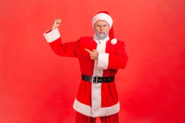 Eu sou forte e posso fazer qualquer coisa. papai noel em pé apontando e mostrando seu bíceps forte.