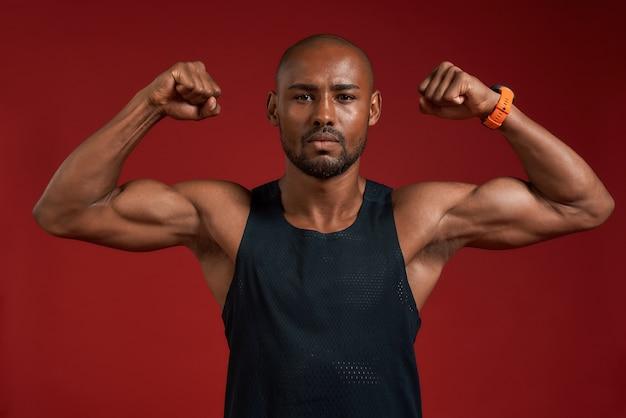 Eu sou forte e saudável, o retrato de um homem afro-americano bonito mostrando seus bíceps e Foto Premium