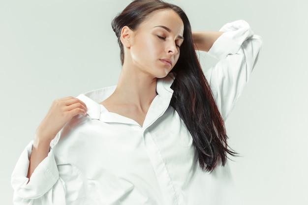 Eu sou jovem e bonita retrato de uma linda garota de cabelos escuros em estúdio cinza