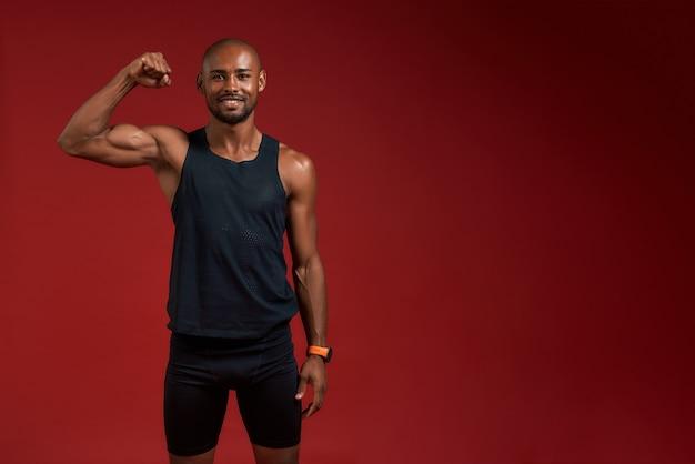 Eu sou o campeão afro-americano bonito mostrando seu bíceps e sorrindo enquanto estou de pé contra