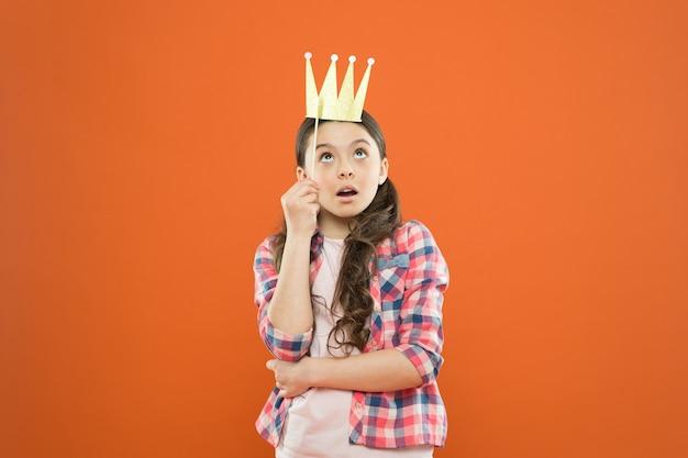 Eu sou um grande chefe aqui. chefezinho em fundo laranja. chefe de linda garota usando coroa de adereço. criança pequena e feliz com grande surpresa no rosto. adorável chefe com grandes sonhos ambiciosos.