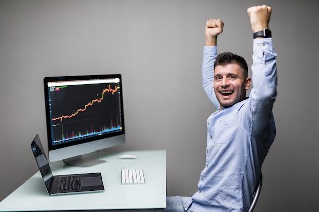 Eu sou um vencedor. feliz jovem comerciante de homem de negócios em trajes formais gritando e se sentindo animado ao olhar para os gráficos de negociação e dados financeiros no escritório.