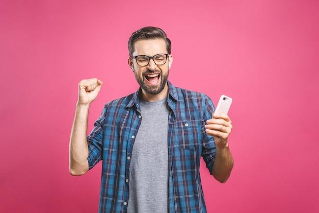 Eu sou um vencedor! homem feliz, segurando o smartphone e comemorando seu sucesso