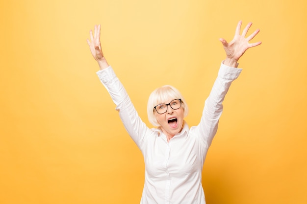Eu sou vencedor! retrato de uma mulher alegre sênior gesticulando vitória isolada sobre fundo amarelo.