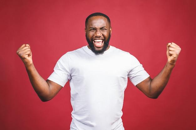 Eu sou vencedor. retrato do homem afro-americano feliz isolado sobre o fundo vermelho.