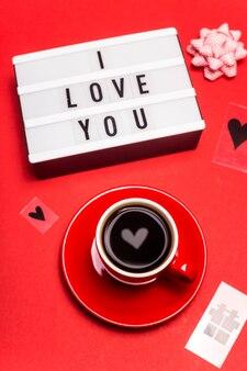 Eu te amo escrito em letras pretas em uma lâmpada decorativa ao lado de uma xícara de café expresso vermelho