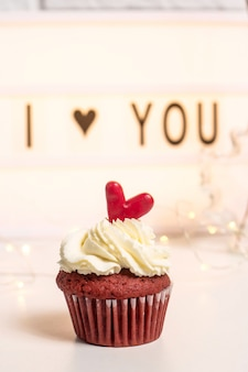 Eu te amo escrito em uma lâmpada decorativa ao lado de cupcakes vermelhos