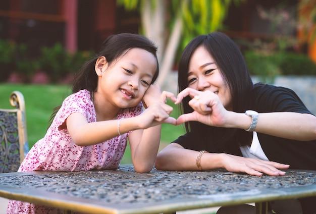 Eu te amo mãe, filha e mãe sorriam com a mão fazem o símbolo do coração.