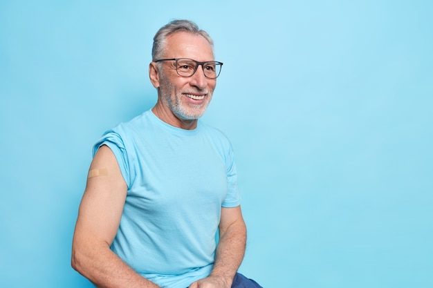 Eu tenho a vacina covid 19. homem idoso barbudo sorridente mostra o ombro com band-aid após a vacinação