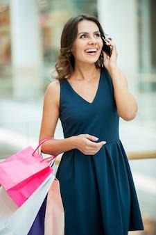 Eu tenho muito à venda. mulher jovem e bonita com um vestido azul segurando sacolas de compras e falando ao celular