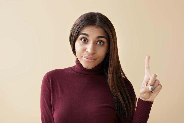 Eu tenho uma ideia! vista recortada de uma jovem mulher morena atraente emocional, fazendo uma expressão facial engraçada e apontando o dedo indicador para cima para chamar sua atenção, tendo um olhar surpreso e animado