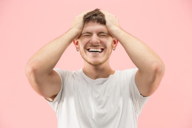 Eu venci. homem feliz de sucesso vencedor comemorando ser um vencedor. imagem dinâmica do modelo masculino caucasiano no fundo rosa do estúdio. vitória, conceito de prazer. conceito de emoções faciais humanas. cores da moda
