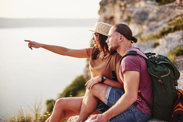 Eu vi algo, você não viu o mesmo. jovem casal descansando de uma caminhada à beira da montanha. quer saber a que distância fica a outra costa.