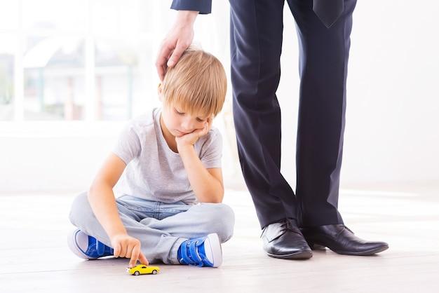 Eu voltarei em breve. menino triste apoiando o rosto na mão enquanto brincava com o carrinho de brinquedo e olhando para baixo enquanto o pai em trajes formais o consolava
